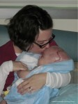 Craniosynostosis -- Alisha kissing Ethan's head;  www.makeoversandmotherhood.com